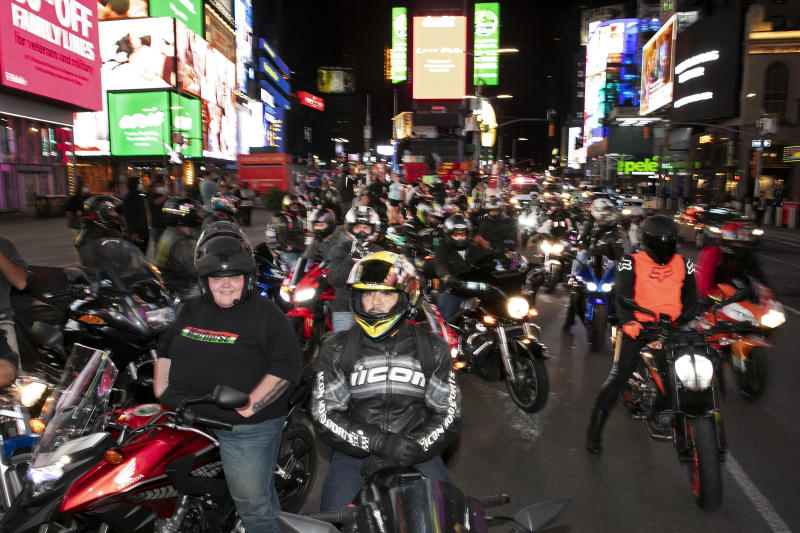 In this Saturday, May 2, 2020 photo, dozens of motorcyclists stop for photos in New York's Times Square during the coronavirus pandemic. Motorcycle enthusiasts normally wouldn't dare rev their engines in Midtown, but now they're eagerly driving into the city to take photos and show off for sparse crowds walking through the commercial hub. (AP Photo/Mark Lennihan)