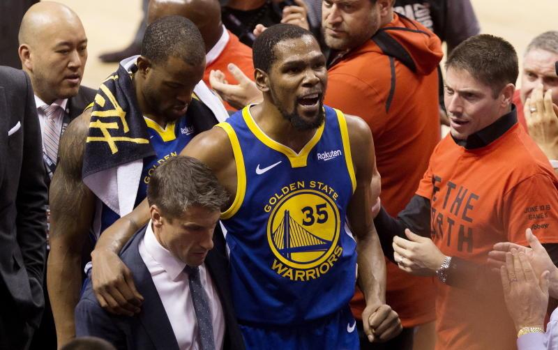 Kevin Durant, alero de los Warriors de Golden State, es ayudado a salir de la cancha tras lesionarse durante el quinto partido de la Final de la NBA ante los Raptors de Toronto, el lunes 10 de junio de 2019 (Chris Young/The Canadian Press via AP)
