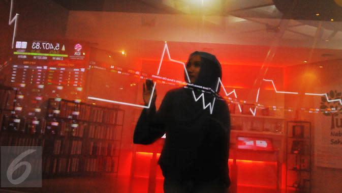 Pengunjung tengah melintasi layar pergerakan saham di BEI, Jakarta, Senin (13/2). Pembukaan perdagangan bursa hari ini, Indeks Harga Saham Gabungan (IHSG) tercatat menguat 0,57% atau 30,45 poin ke level 5.402,44. (Liputan6.com/Angga Yuniar)