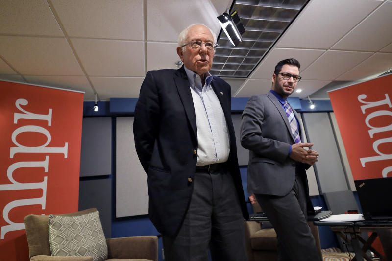 Democratic presidential candidate Sen. Bernie Sanders, I-Vt., left, speaks with people in the audience as moderator Peter Biello, right, looks on following a forum broadcast on radio in a New Hampshire Public Radio station, Sunday, Jan. 19, 2020, in Concord, N.H. (AP Photo/Steven Senne)