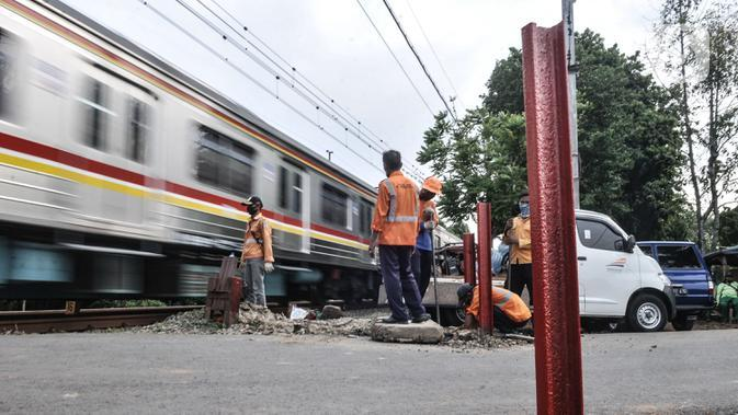 Pekerja PT KAI menyelesaikan pemasangan pembatas jalan di perlintasan kereta tanpa palang pintu di kawasan TPU Tanah Kusir, Jakarta, Kamis (17/9/2020). Sebelumnya pada Kamis (17/9) pagi terjadi kecelakaan yang melibatkan sebuah mobil dan KRL di perlintasan tersebut. (merdeka.com/Iqbal S. Nugroho)