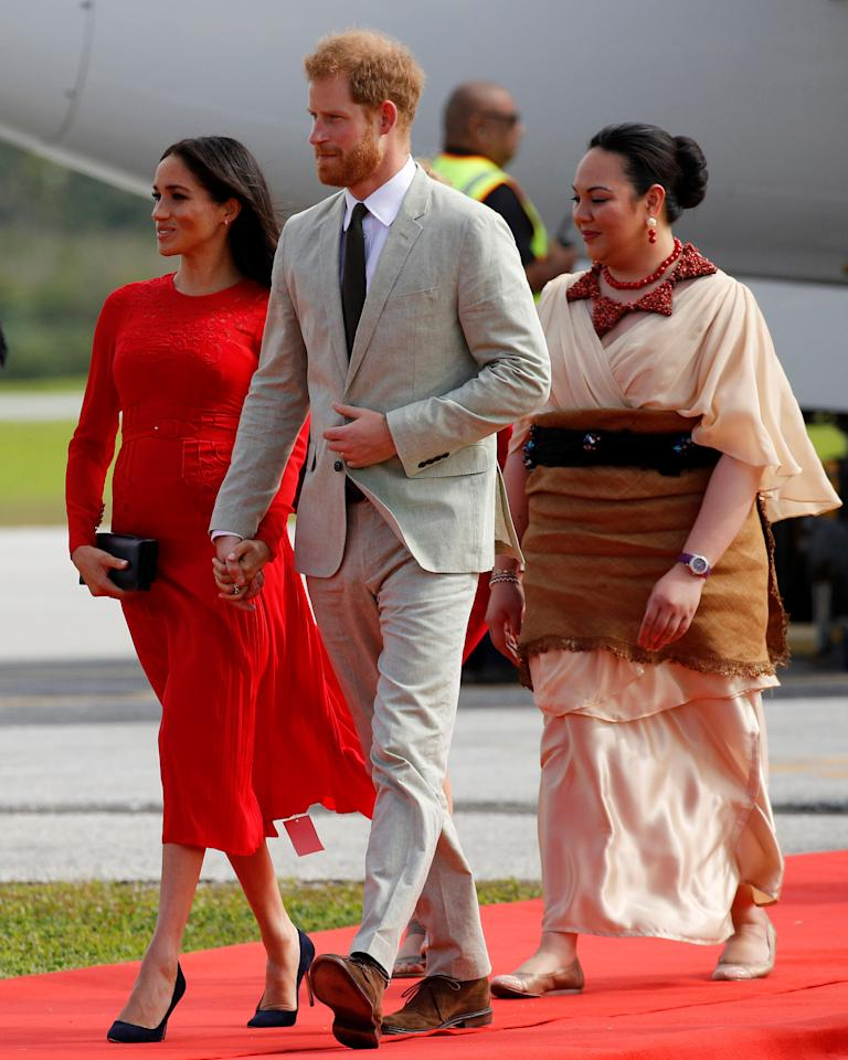 <p>As the Duke and Duchess of Sussex walking off their plane, eagle-eyed royal watchers noticed a tag hanging off the hem of pregnant Meghan's Self Portrait dress. Photo: Reuters </p>