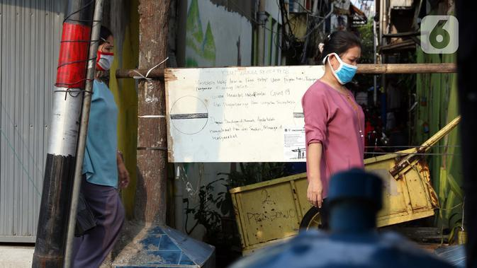 Warga berjalan di salah satu gang yang ditutup secara mandiri di kawasan Duri, Jakarta, Sabtu (4/4/2020). Penutupan akses masuk kawasan ini untuk membatasi kegiatan warga dan mencegah penyebaran serta penularan virus COVID-19. (Liputan6.com/Helmi Fithriansyah)