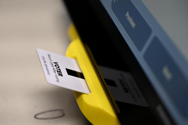 An electronic card with ballot information is seen inserted in a voting machine, Tuesday, Nov. 5, 2019, in Dallas, Ga. New voting machines that combine touchscreens with paper ballots are getting a limited test run in Georgia, as officials rush to meet a court-ordered deadline to retire the old system before any votes are cast in 2020. (AP Photo/Mike Stewart)