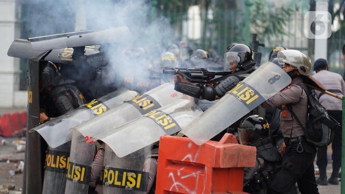 Polisi menembakkan gas air mata saat terlibat bentrok dengan pengunjuk rasa di Jalan Medan Merdeka Timur, Jakarta, Kamis (8/10/2020). Bentrokan terjadi akibat massa yang memaksa masuk ke depan Istana Negara untuk berunjuk rasa terkait penolakan UU Cipta Kerja. (Liputan6.com/Immanuel Antonius)
