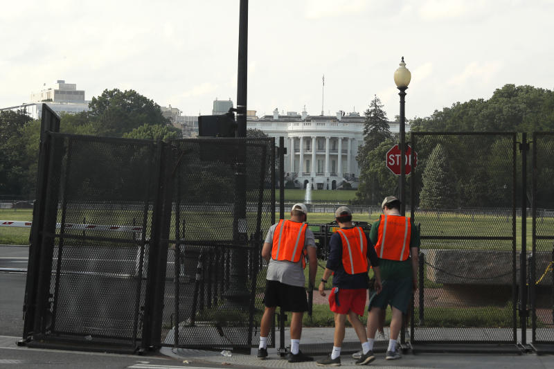 FILE - In this June 10, 2020, file photo workers remove a security fence near the White House in Washington. The fence was erected as protests over the death of George Floyd, a black man who was in police custody in Minneapolis, moved to Washington. Americans are deeply unhappy about the state of their country, and a majority think President Donald Trump is doing more to divide the nation than unite it, according to a new poll from The Associated Press-NORC Center for Public Affairs Research. (AP Photo/Maya Alleruzzo, File)