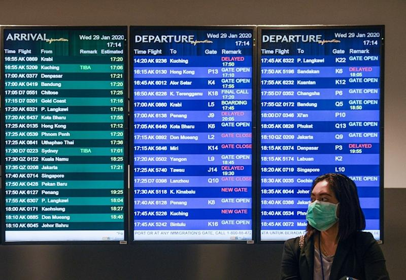 A woman wearing face mask stands in front of the flight information screen at KLIA2 in Sepang January 29, 2020. — AFP pic