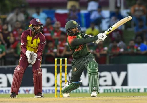 West Indies keeper Denesh Ramdin (L) watches Liton Das (R) of Bangladesh hit a six in a career-best innings of 61 off just 32 balls with six fours and three sixes