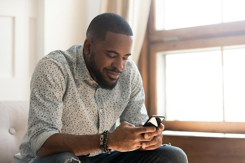 Young african american man holding smartphone texting message or play mobile game sit on sofa at home, smiling millennial black guy using social media app messenger, surfing web on phone indoors
