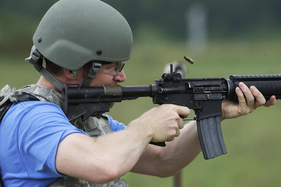 NASCAR driver Dale Earnhardt Jr. fires a M4 Rifle at Camp Atterbury Wednesday, July 23, 2014, in Edinburgh, Ind. (AP Photo/Darron Cummings)