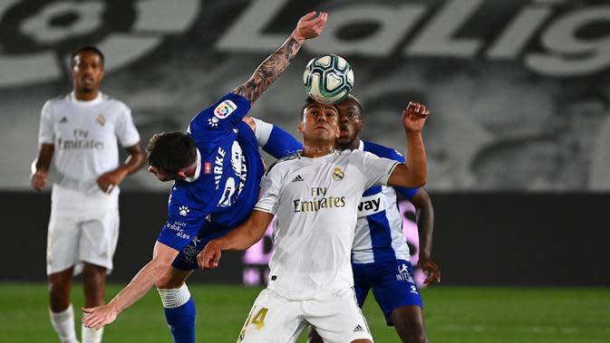 Gelandang Real Madrid, Casemiro, berebut bola dengan gelandang Alaves, Oliver Burke, pada laga lanjutan La Liga pekan ke-35 di Stadion Alfredo di Stefano, Sabtu (11/7/2020) dini hari WIB. Real Madrid menang 2-0 atas Alaves. (AFP/Gabriel Bouys)
