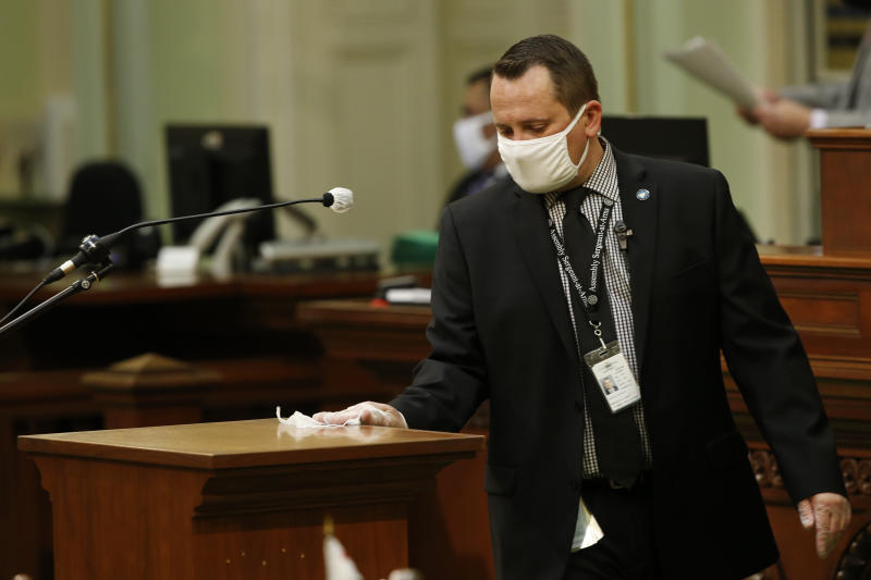 Assembly Sgt.-at-Arms Larry Williams disinfects the podium after its use by an Assembly member at the Capitol in Sacramento, Calif., Monday, June 8, 2020. The Assembly held its first full session, Monday, since going into a recess in March due to the coronavirus pandemic. (AP Photo/Rich Pedroncelli)