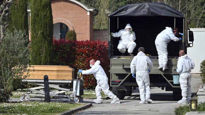 Petugas membawa peti mati berisi jasad korban virus corona COVID-19 yang diturunkan dari truk militer di pemakaman Ferrara, Italia, Sabtu (21/3/2020). Italia menghadapi krisis paling parah sejak Perang Dunia II. (Massimo Paolone/LaPresse via AP)