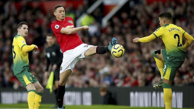 Gelandang Manchester United, Nemanja Matic berebut bola dengan bek Norwich City, Aarons pada pertandingan lanjutan Liga Inggris di Old Trafford (11/1/2020). MU menang telak 4-0 atas Norwich. (Martin Rickett/PA via AP)
