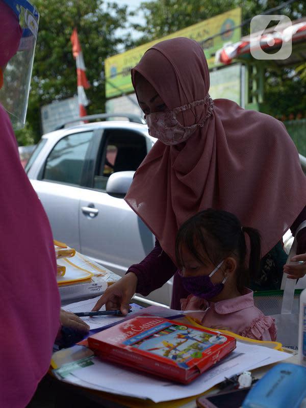 Wali murid mengambil tugas sekolah secara drive-thru dari guru SDIT Ibnu Sina di Jakarta, Rabu (26/8/2020). Selama pembelajaran jarak jauh, siswa diwajibkan mengambil dan mengembalikan tugas di sekolah. (merdeka.com/Imam Buhori)