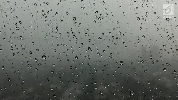 Tetesan air hujan yang ada di jendela kaca dengan latar belakang mendung menyelimuti langit Jakarta, Kamis (1/2). BMKG juga meminta warga mengantisipasi potensi angin berkecepatan tinggi. (Liputan6.com/Immanuel Antonius)