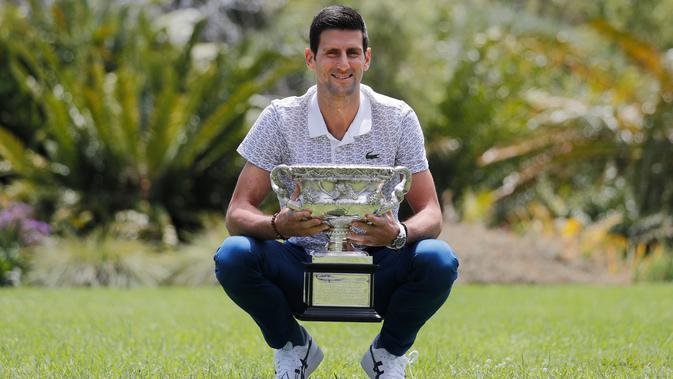Petenis Serbia, Novak Djokovic berpose dengan piala juara tunggal putra Australia Terbuka 2020 saat sesi pemotretan di Royal Botanic Gardens Victoria, Melbourne, Australia, Senin (3/2/2020). Bagi Novak Djokovic, ini merupakan gelar Australia Terbuka kedelapan. (AP Photo/Dita Alangkara)