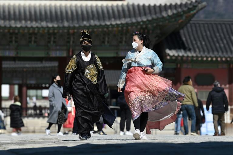 Visitors wearing traditional Korean hanbok dresses also donned face masks at Gyeongbokgung palace in Seoul as fears for the coronavirus mounted