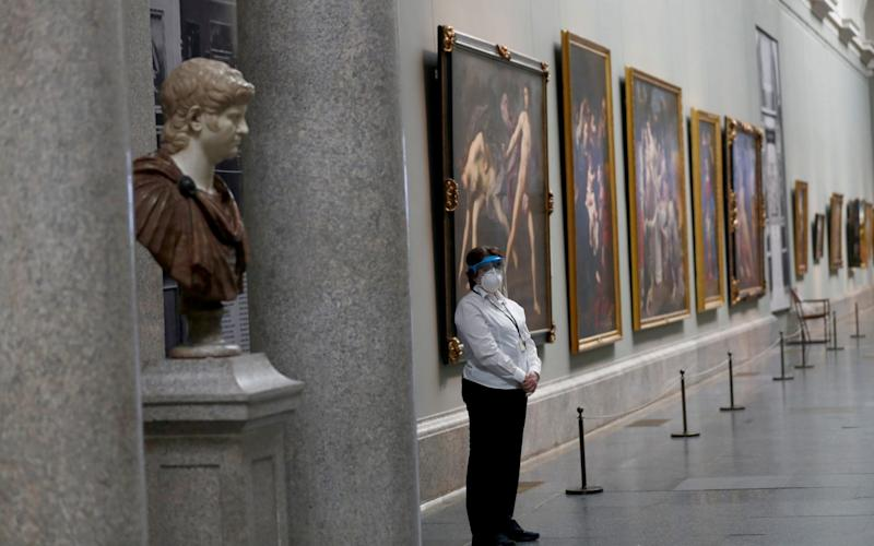 A museum worker wears a protective mask as the Prado museum prepares for reopening - Reuters