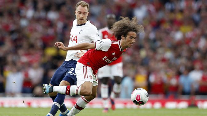 Gelandang Arsenal, Matteo Guendouzi melewati gelandang Tottenham Hotspur, Christian Eriksen selama pertandingan Liga Inggris di stadion Emirates di London (1/9/2019). Arsenal bermain imbang 2-2 atas Tottenham. (AP Photo/Alastair Grant)