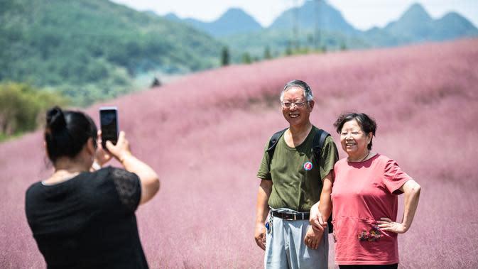 Wisatawan berpose di tengah padang rumput berwarna pink (Muhlenbergia capillaris) di objek wisata Shenquangu di Wilayah Changshun, Provinsi Guizhou, China barat daya (2/9/2020). (Xinhua/Tao Liang)