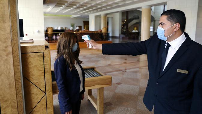 Seorang karyawan hotel membersihkan sebuah meja di Hotel Conrad di Kairo, Mesir pada Selasa (2/6/2020). Pemerintah Mesir mulai mengizinkan puluhan hotel beroperasi kembali untuk melayani wisatawan lokal dengan kapasitas dibatasi 50 persen. (Xinhua/Ahmed Gomaa)