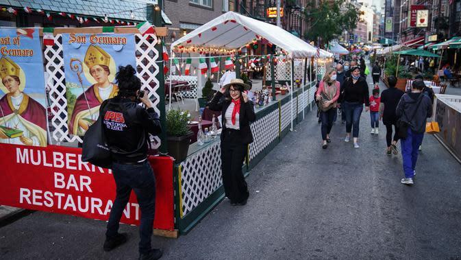 Orang-orang berjalan melalui di mana restoran mengoperasikan area luar ruangan (outdoor) hingga ke trotoar dan jalanan di New York, 3 Oktober 2020. Kota itu mengizinkan restoran membuat area makan outdoor sebagai upaya mengatasi dampak ekonomi COVID-19 yang berkelanjutan. (AP Photo/John Minchillo)