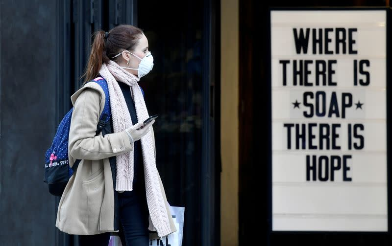 A woman wearing a protective face mask walks past a shop, as the spread of the coronavirus disease (COVID-19) continues, in London