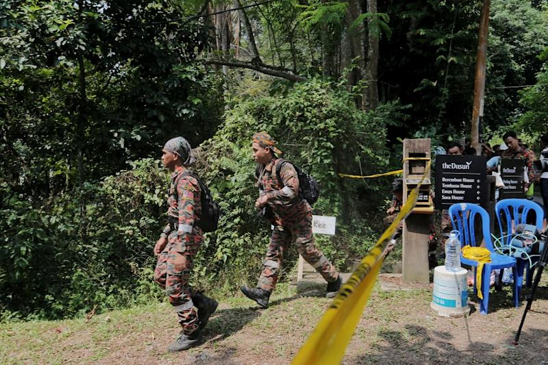Members of the search team are seen entering an area cordoned by police after the discovery of a body in the jungle near Seremban August 13, 2019. — Picture by Ahmad Zamzahuri