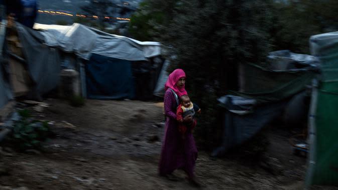 Seorang wanita imigran menggendong bayinya berjalan di luar kamp pengungsi di pulau Samsos, Yunani (13/11/2019). Ribuan imigran berjuang untuk menemukan ruang di perbukitan di atas kota, membuat rumah sementara dari bahan bangunan apa pun yang dapat mereka temukan. (AFP Photo/Angelos Tzortzinis)