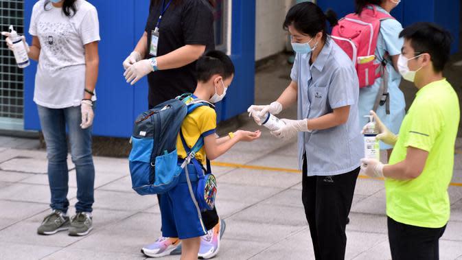 Seorang murid mendisinfeksi tangannya sebelum memasuki sekolah di Tsuen Wan, Hong Kong, China selatan, pada 29 September 2020. Aturan menjaga jarak sosial (social distancing) sebagian telah dilonggarkan dan kehidupan masyarakat mulai kembali normal. (Xinhua/Lo Ping Fai)