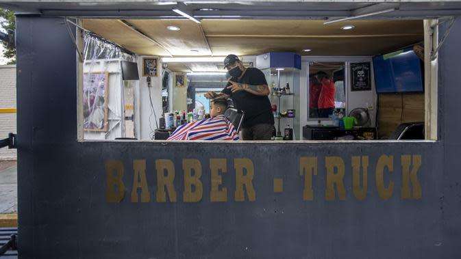 Gerardo (kanan) memangkas rambut pelanggan dalam salon rambut keliling miliknya di Mexico City, Meksiko, 6 Agustus 2020. Gerardo mengubah sebuah mobil van menjadi salon rambut keliling yang menawarkan jasa pangkas rambut kepada warga Mexico City di tengah pandemi COVID-19. (Xinhua/Ricardo Flores)