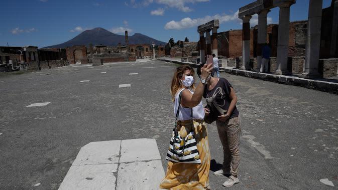 Dua perempuan berswafoto saat mengunjungi situs arkeologi Pompeii usai kebijakan lockdown selama dua bulan untuk mengendalikan penyebaran Covid-19 di Italia, Selasa (26/5/2020). Salah satu situs arkeologi paling terkenal di dunia ini dibuka kembali untuk umum pada 26 Mei. (AP/Alessandra Tarantino)