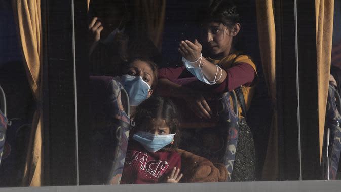 Pengungsi dan migran berangkat dengan bus setelah kedatangan mereka di pelabuhan Lavrio, sekitar 75 kilometer (48miles) selatan Athena (29/9/2020). Pemindahan sebagai bagian dari upaya untuk memperbaiki kondisi di kamp pulau yang penuh sesak. (AP Photo/Petros Giannakouris)