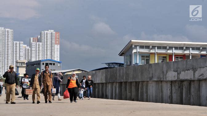 Wisatawan berjalan di dekat tanggul laut di Pelabuhan Kali Adem, Muara Angke, Jakarta, Selasa (12/2). Pembangunan tanggul laut tersebut merupakan bagian dari program Pengembangan Terpadu Pesisir Ibukota Negara atau NCICD. (Merdeka.com/Iqbal S. Nugroho)