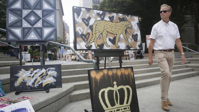 Seorang pria mengamati karya seni yang dipajang di area terbuka dalam pameran Art Downtown, Vancouver, British Columbia, Kanada, 4 September 2020. Art Downtown merupakan proyek yang memungkinkan seniman dan publik saling terhubung dan menginspirasi serta berbagi kreativitas. (Xinhua/Liang Sen)