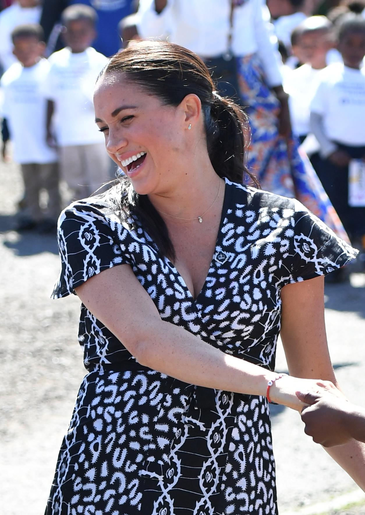 The Duchess of Sussex joins in with dancers as she leaves the Nyanga Township in Cape Town, South Africa, on the first day of their tour of Africa. (Photo by Dominic Lipinski/PA Images via Getty Images)