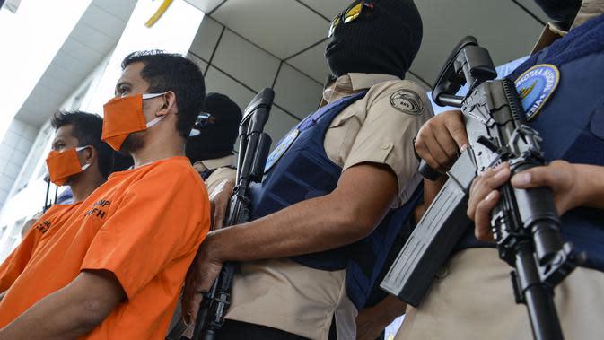 Petugas Badan Narkotika Nasional Indonesia (BNN) mengawal dua pria lokal yang diduga menyelundupkan sabu pada konferensi pers di Banda Aceh (13/10/2020). (AFP Photo/Chaideer Mahyuddin)