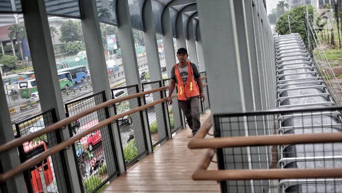 Pekerja melintas di jembatan penyeberangan orang (JPO) Bundaran Senayan, Jakarta, Senin (21/1). (Liputan6.com/Faizal Fanani)