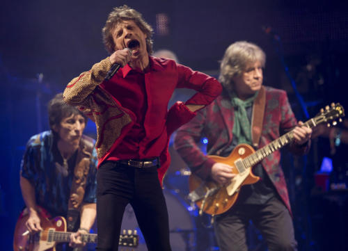 Mick Jagger, center, Ronnie Wood, left, and Mick Jones of British band the Rolling Stones perform on the Pyramid main stage at Glastonbury, England, Saturday, June 29, 2013. Thousands of music fans have arrived for the festival to see headliners, Arctic Monkeys, Mumford and Sons and the Rolling Stones.(Photo by Joel Ryan/Invision/AP)