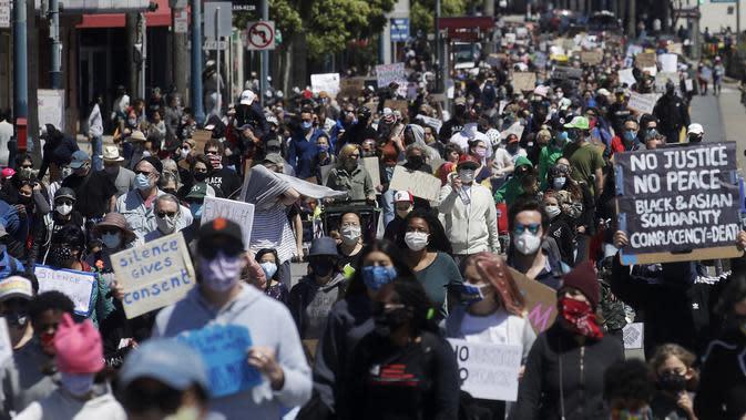 Pengunjuk rasa yang memprotes kematian George Floyd berbaris di Ocean Avenue, San Francisco, Amerika Serikat, Minggu (7/6/2020). Gelombang protes atas kematian George Floyd terus mengguncang Amerika Serikat. (AP Photo/Jeff Chiu)