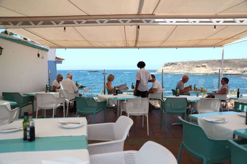 """Waiter Yamilca attends tourists in a terrace of an almost empty restaurant """"Celso"""" at La Caleta beach in Adeje"""