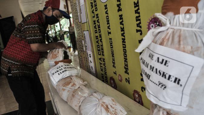 Pekerja memasang boneka pocong dan peti mati di Kantor Kecamatan Senen, Jakarta, Kamis (13/8/2020). Pemkot Jakpus menyiapkan peti mati dan boneka pocong di setiap kecamatan sebagai peringatan akan bahaya Covid-19 dan imbauan untuk tidak mengabaikan protokol kesehatan. (merdeka.com/Iqbal Nugroho)