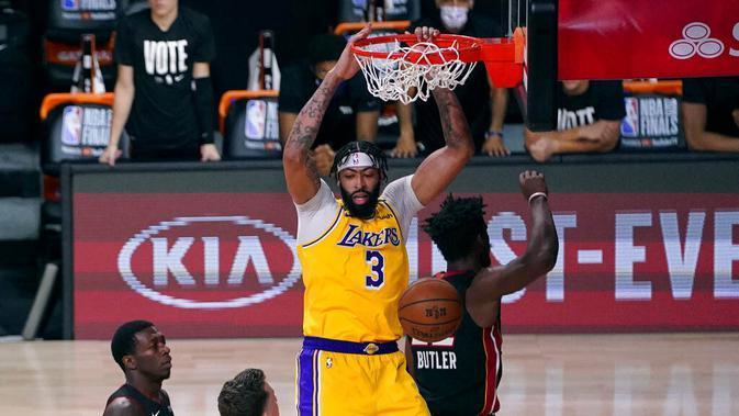 Pebasket Los Angeles Lakers, LeBron James, berusaha melewati pebasket Miami Heat pada gim pertama final NBA di Lake Buena Vista, Kamis (1/10/2020). Lakers menang dengan skor 116-98. (AP Photo/Mark J. Terrill)