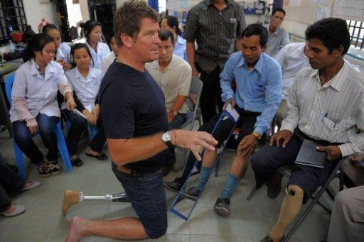 """Canadian trainer Stephen Sumner (C) teaches amputees during their first mirror therapy training session at the Cambodia Trust. Sumner explains that the reflection of the intact limb can fool the brain into """"seeing"""" two healthy legs, allowing it to once again send command signals to the phantom leg"""