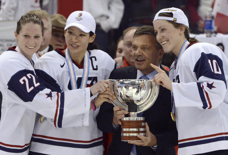 FILE - In this April 9, 2013, file photo, United States' Kacey Bellamy, Julie Chu and Meghan Duggan, from left, stand with IIHF president Rene Fasel as they are presented with the trophy after the U.S. team defeated Canada 3-2 in the gold medal game at the women's ice hockey world championships in Ottawa, Ontario. The women's world hockey championships in Canada have been canceled because of the new coronavirus. International Ice Hockey Federation President René Fasel tells The Associated Press the decision was made by conference call Saturday, March 7, 2020. (Sean Kilpatrick/The Canadian Press via AP, File)