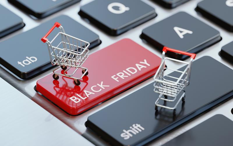 Modern computer keyboard with a shopping carts and a red Black Friday button. Horizontal composition with selective focus and copy space. Great use for shopping and Cyber Monday related concepts.