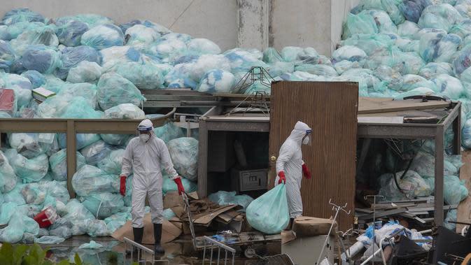 Petugas medis mengenakan alat pelindung diri saat membuang limbah biologis berbahaya di luar Rumah Sakit del Instituto Mexicano del Seguro Social, Veracruz, Meksiko, Rabu (12/8/2020). Pembuangan limbah medis yang tidak tepat menjadi masalah di tengah pandemi COVID-19. (AP Photo/Felix Marquez)