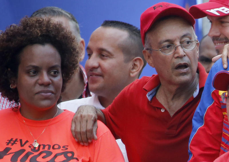 FILE - In this April 6, 2019 file photo, Luis Alfredo Motta Dominguez, right, attends a pro-government rally in Caracas, Venezuela. On Thursday, March 26, 2020, the U.S. Justice Department made public it has charged in several indictments against Venezuelan President Maduro and his inner circle, including Motta, that the leader has effectively converted Venezuela into a criminal enterprise at the service of drug traffickers and terrorist groups as he and his allies stole billions from the South American country.  (AP Photo/Ariana Cubillos, File)