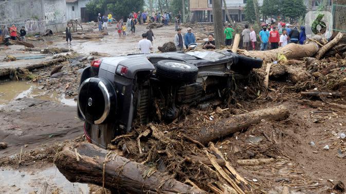 Sebuah mobil terguling usai banjir bandang melanda Kampung Cibuntu, Desa Pasawahan, Kecamatan Cicurug, Sukabumi, Jawa Barat, Selasa (22/9/2020). Data sementara puluhan bangunan rusak berat, 12 rumah hanyut, dan dua korban hilang masih dicari. (merdeka.com/Arie Basuki)